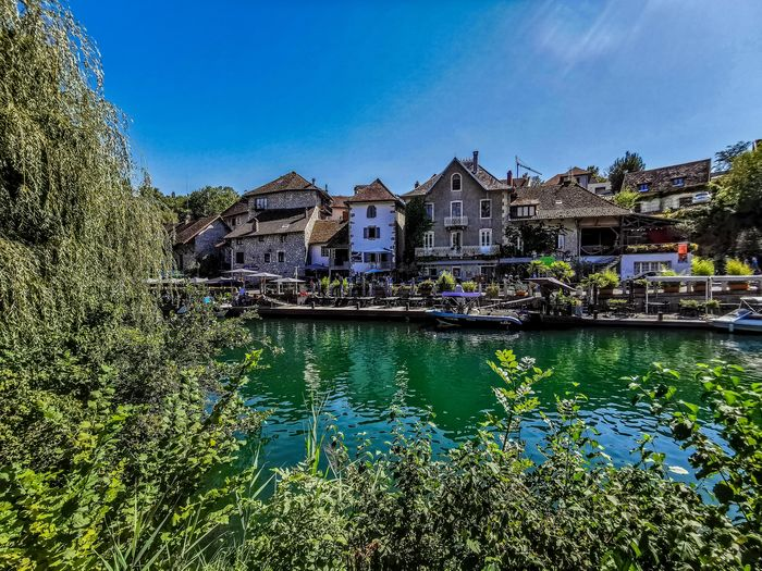 Houses by river and buildings against blue sky