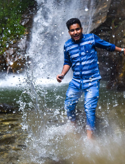 Adult Adults Only Casual Clothing Cheerful Day Enjoyment Full Length Fun Happiness Motion Nature One Man Only One Person Only Men Outdoors People Real People Refreshment Smiling Splashing Spraying Water Wet Young Adult