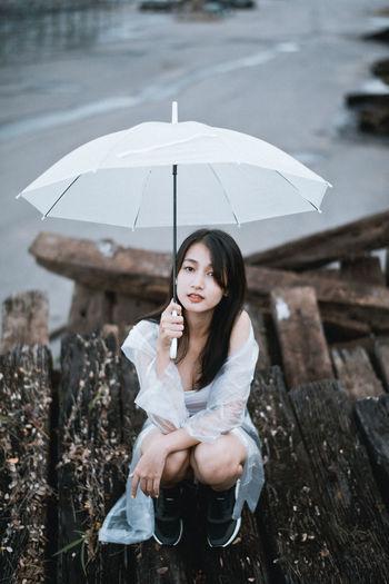 Portrait of woman sitting in rain