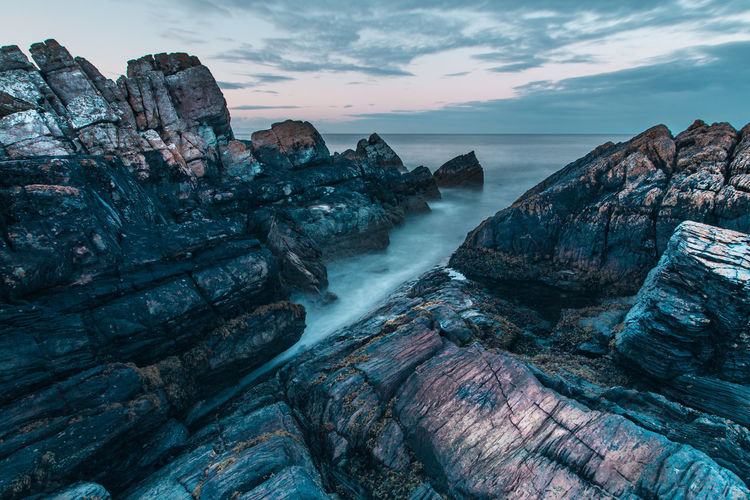 High angle view of rock formations in sea against cloudy sky during sunset