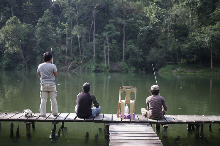 Rear view of men fishing in lake