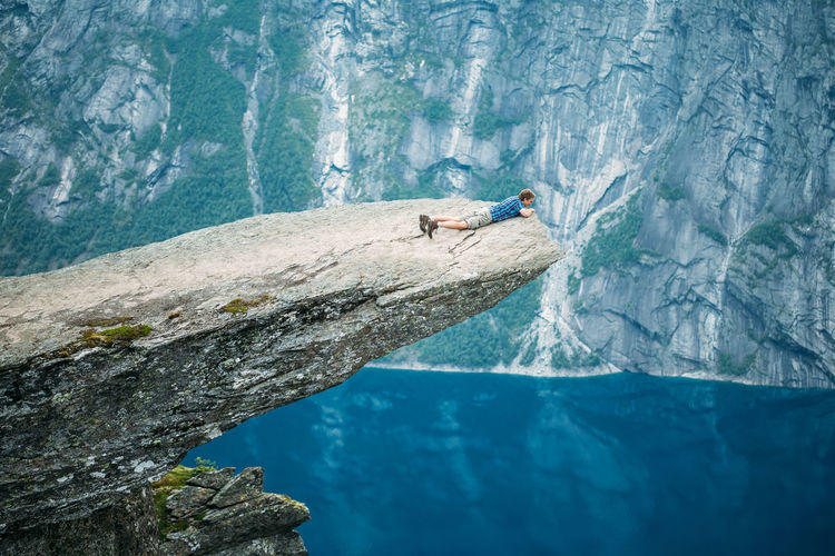 Man Lying On Cliff By Sea