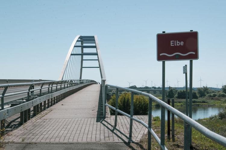 Information sign on bridge against sky