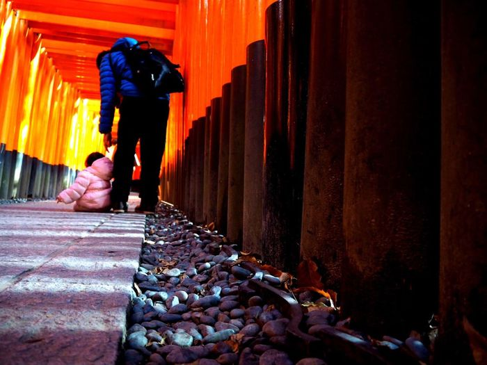 Rear View Of Woman With Child In Torii Gate