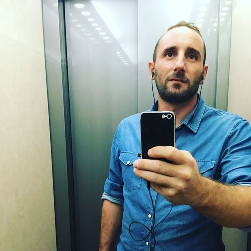 Man using mobile phone against elevator