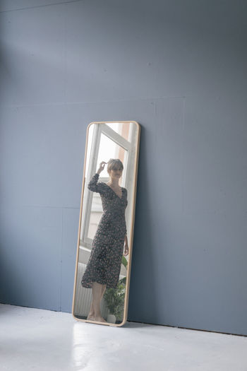 Woman looking through window on wall