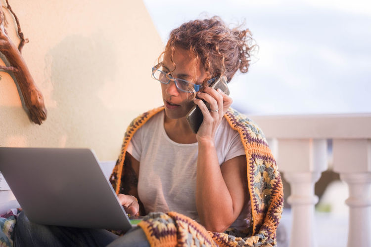 Woman using mobile phone and laptop while sitting at home