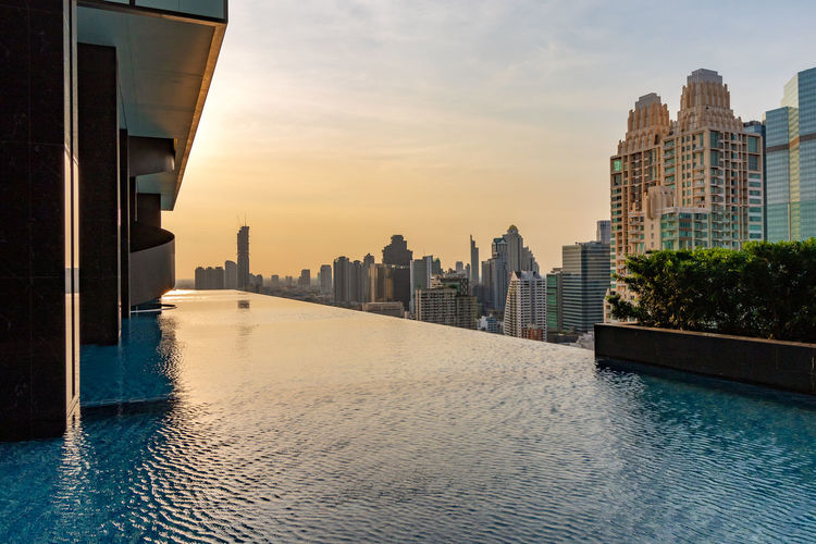 Infinity pool by modern buildings in city against sky during sunset