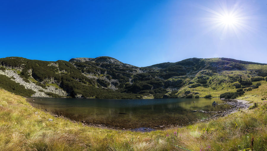Panoramic view on mountain lake in front of mountain range, Rila national park, Iontchevo lake, Bulgaria Relaxing Bulgaria Rila Hot Summer Park National Park Day Lens Flare Idyllic Mountain Range Blue Sun Nature Reflection Sunlight Lake Tranquility Sky Water Mountain