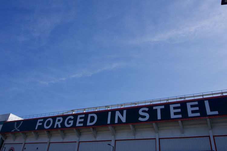 'Forged in Steel' at Bramall Lane Football Ground, Sheffield United. Sheffield Sheffield United Bramall Lane Football Stadium Ground Standing Yorkshire Blades Text Western Script Low Angle View Capital Letter Architecture Blue Sky Built Structure No People Building Exterior Sign Day Information Sign Copy Space Script