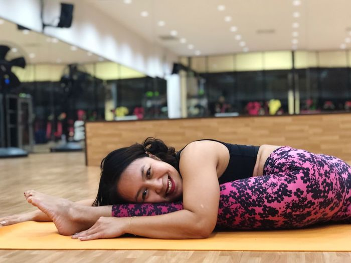 Smiling Fitness Yogapose Yoga Lying Down One Person Relaxation Young Adult Lifestyles Indoors  Adult Leisure Activity Young Women Women Real People Healthy Lifestyle Resting Wellbeing Exercising Sport Lying On Front Eyes Closed