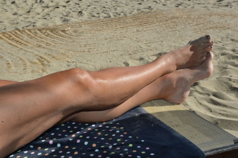 Low section of woman lying on sand