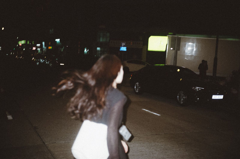 Woman standing by car on street at night