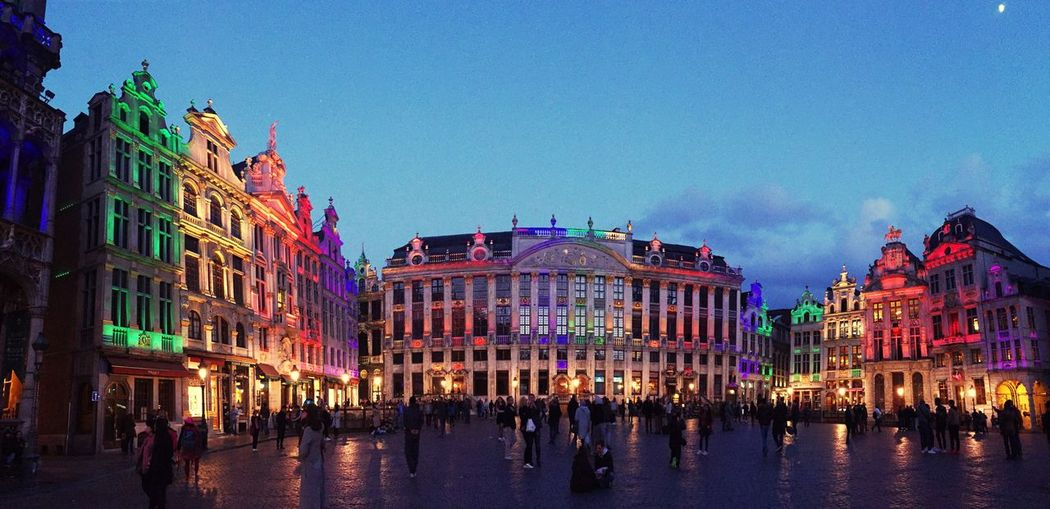 People by illuminated grand place at dusk