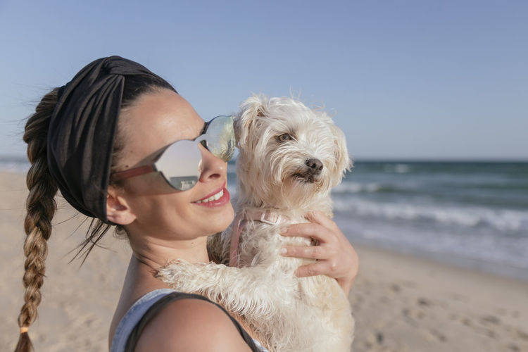 Portrait of young woman with dog on beach