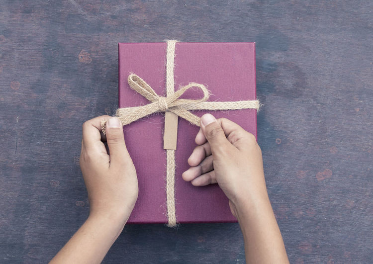 Cropped image of hands tying ribbon on gift
