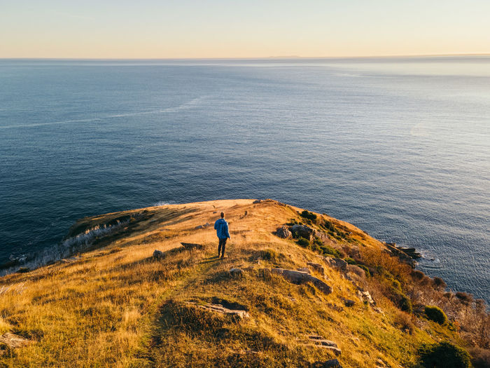 Rear view of man looking at sea while standing at cliff
