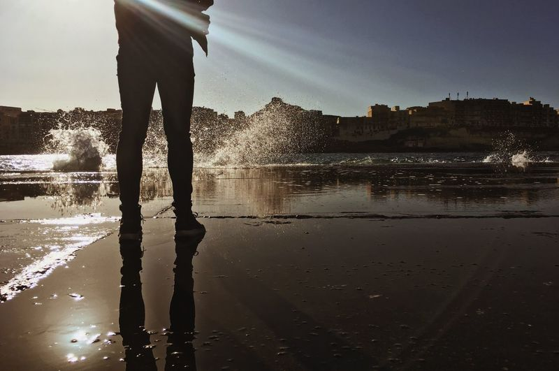 Low section of silhouette man standing in water