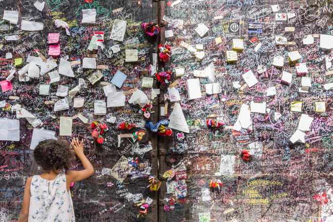 Love notes at Juliet's house in Verona italy. A little girl look the attached messages. Background Chewing Child Closeup Culture Europe Famous Giulietta Graffiti Gum House Italy Juliet  Letter Look Love Lover Message Messages Notes Paper Pattern Place Romeo Shakespeare