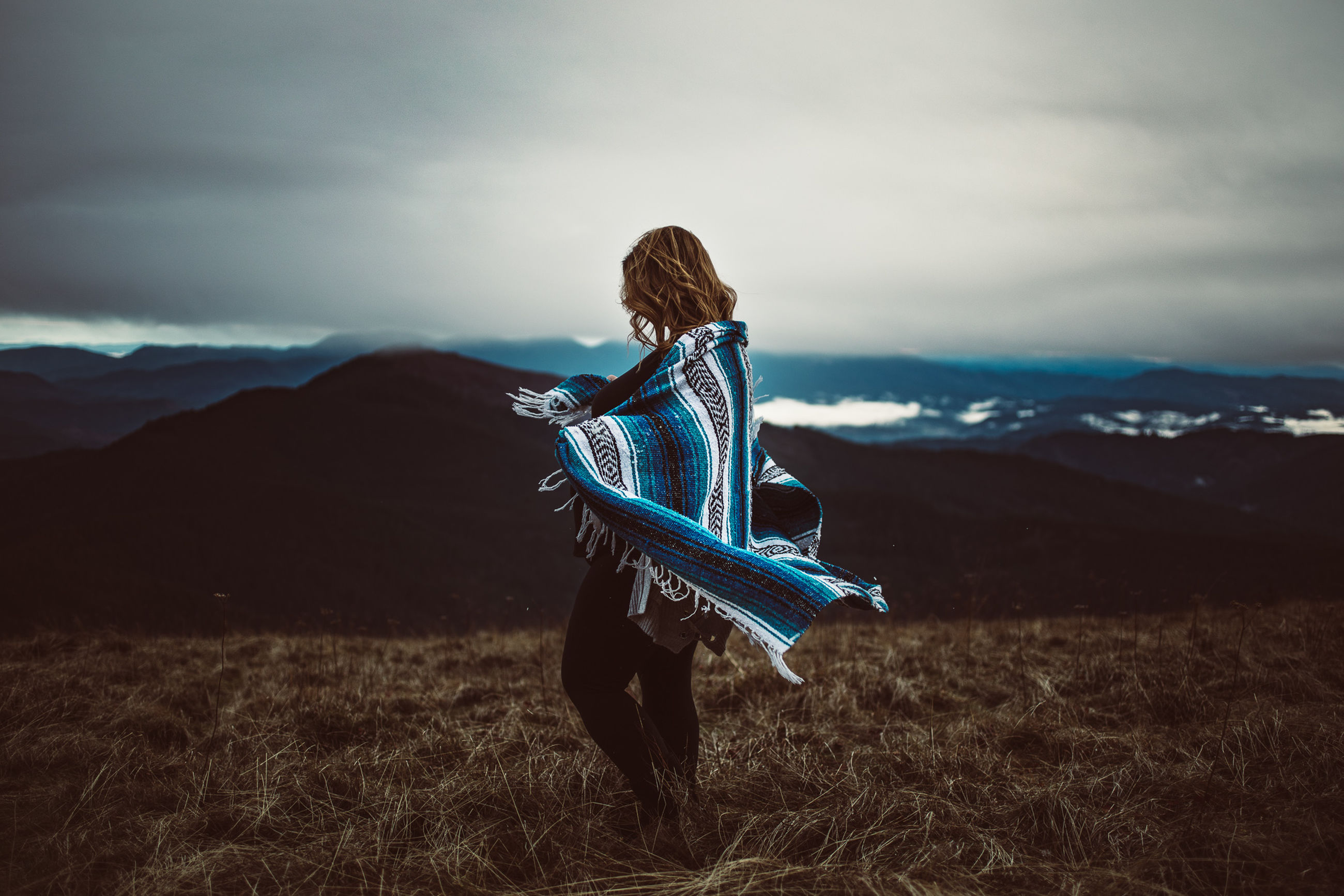 sky, field, one person, land, real people, cloud - sky, mountain, leisure activity, nature, beauty in nature, lifestyles, tranquility, environment, landscape, women, tranquil scene, adult, standing, non-urban scene, hairstyle, hair, outdoors