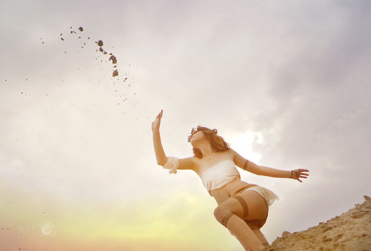 Woman Throwing Sand At Beach Against Sky During Sunset