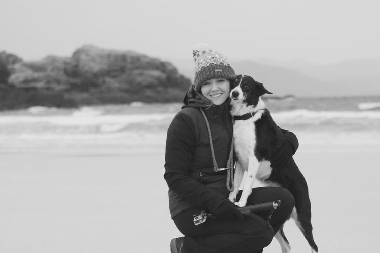 Portrait of smiling woman with dog at beach during winter