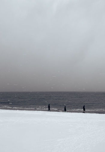People on snow covered land and sea against sky