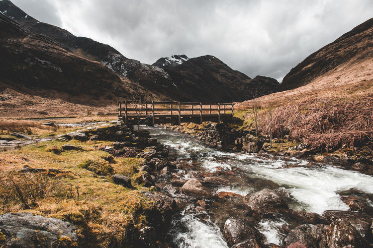 Bridge over stream by mountains against sky