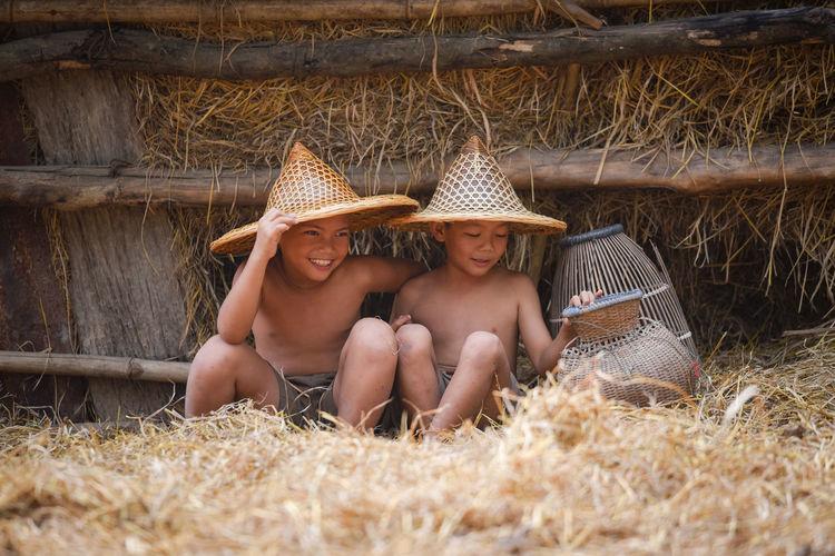 Boys sitting on hay