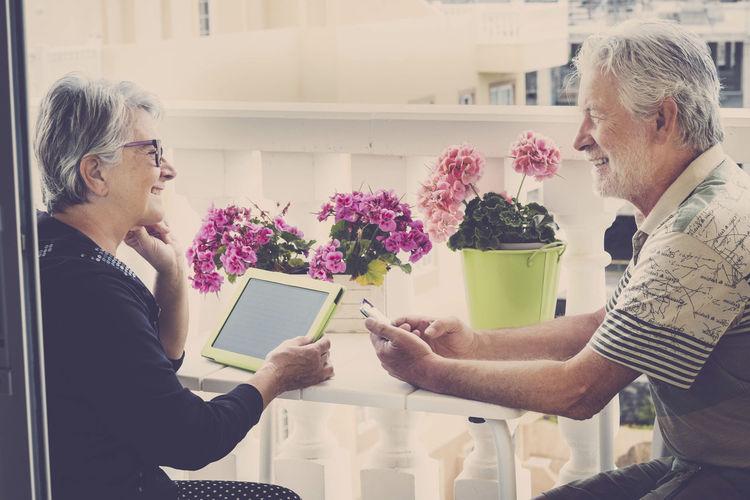 Smiling Senior Couple Sitting On Balcony