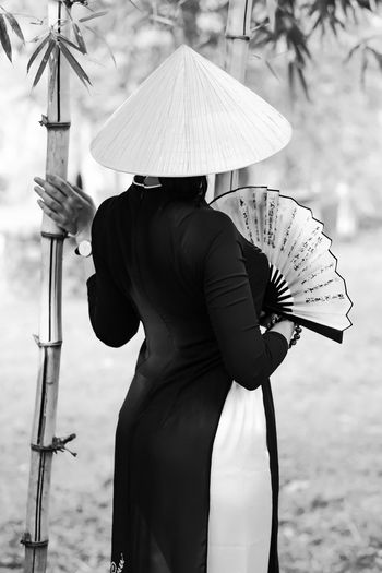 Rear view of woman holding hand fan while standing by bamboo plant