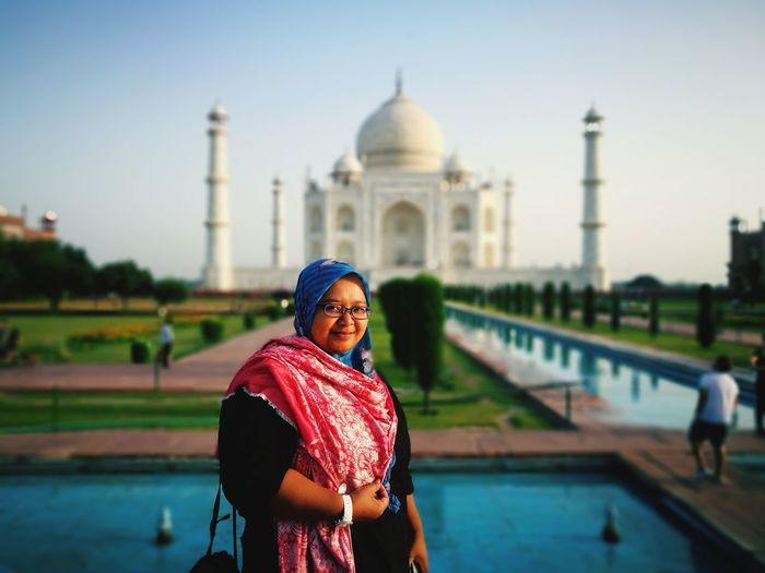 Portrait of smiling woman standing against taj mahal