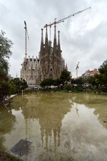 Barcelona, Spain - April 4, 2016: Sagrada Familia, is a large Roman Catholic church in Barcelona, designed by Spanish architect Antoni Gaudi. Unesco World Heritage Site. Spain Ancient Architecture Antoni Gaudí Barcelona, Spain Basilica City Cloudy Sky Construction Crane Construction Site Editorial  Europe Famous Place Gothic Architecture History Landmark Monument Outdoors Reflection Religious Architecture Roman Catholic Church Sagrada Familia Skyscraper SPAIN Travel Destinations UNESCO World Heritage Site Waterside
