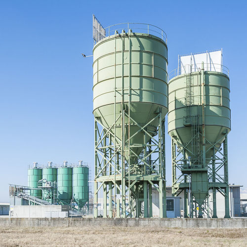 Low Angle View Of Industrial Silos Against Blue Sky