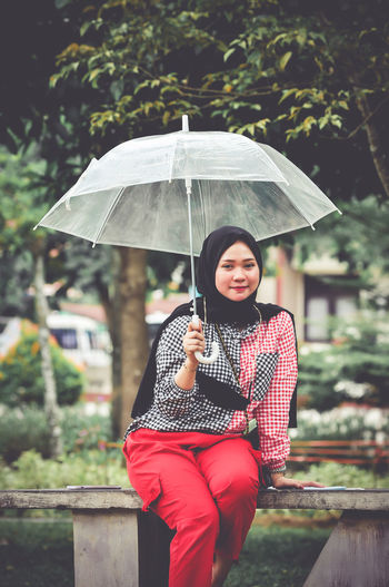 Portrait of woman with umbrella standing in rain during rainy season