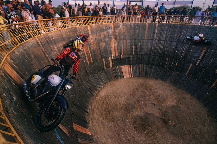 The pit of Death: Stuntmen in rural India ride their motorcycles in the pit of death, and collect the equivalent of a few cents in tips from bystanders. The Photojournalist - 2018 EyeEm Awards Adult Adventure Architecture Crash Helmet Day Full Length Group Of People Headwear Helmet High Angle View Land Vehicle Leisure Activity Men Mode Of Transportation Motion Motorcycle Nature Outdoors People Sport Sports Helmet Transportation