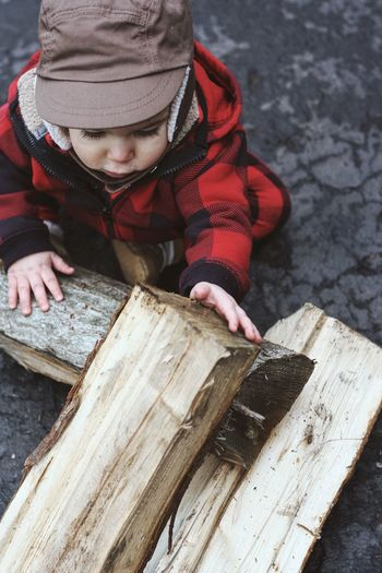 Cute toddler playing with firewood outdoors