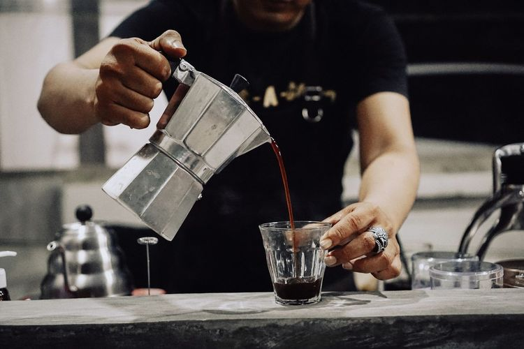 Midsection of barista preparing coffee at cafe