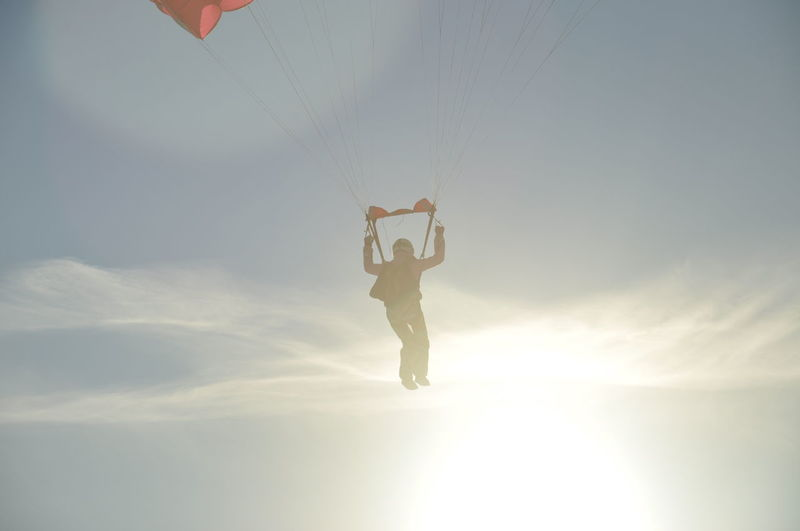 Low Angle View Of Man Paragliding In Sky