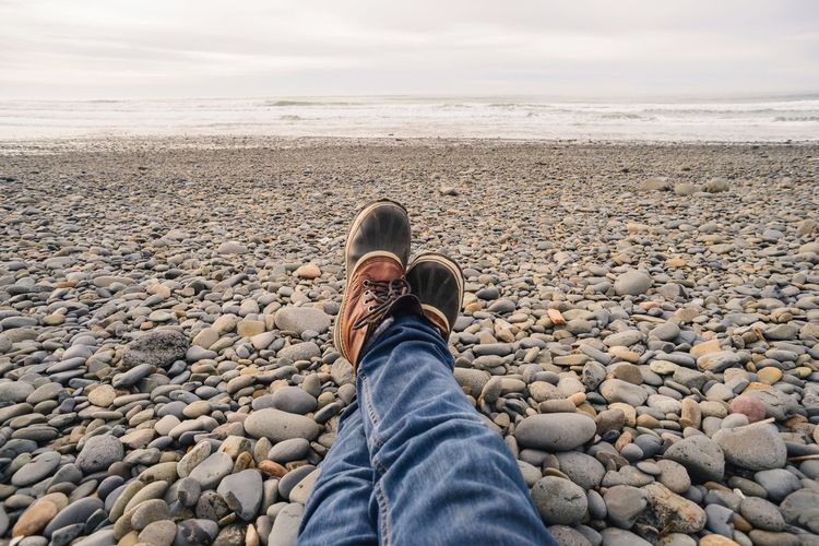 Low Section Of Man Sitting On Pebbles At Beach