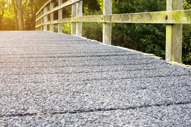 Selective focus of cement bridge with wooden rack walkway along to the forest Bridge Cement Wooden Walkway Road Footpath Surface Level Nature Direction Transportation Plant Day Outdoors Street Concrete Built Structure The Way Forward Forest Trail Across Forward Ground