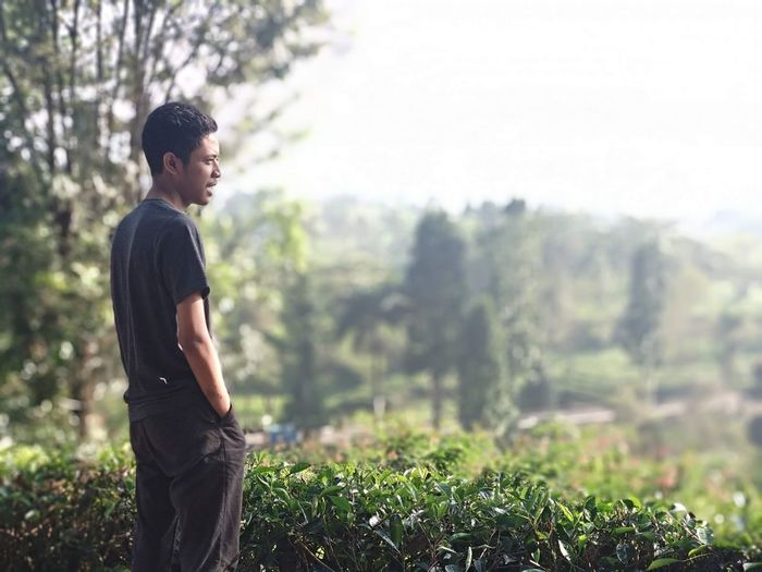Side view of young man looking away against plants