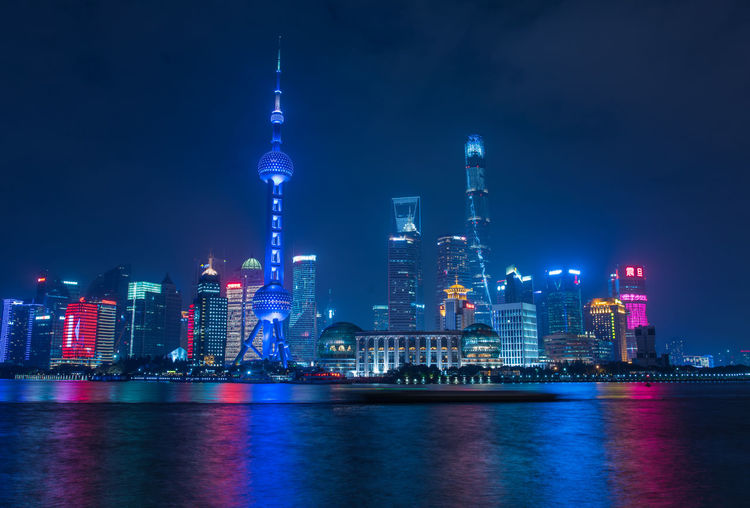 River Against Illuminated Oriental Pearl Tower In City At Night