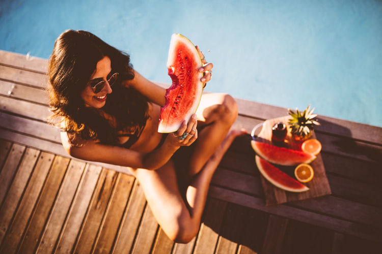 Young woman holding watermelon against water