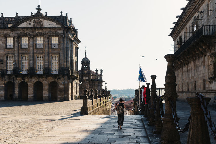 Unidentified woman is walking alone by empty obradoiro square in santiago during pandemic