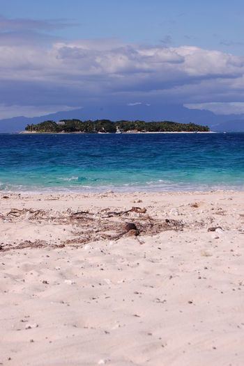 A view of another tropical Island Sea Beach Water Sky Land Beauty In Nature Scenics - Nature Tranquility Tranquil Scene Cloud - Sky Nature No People Day Idyllic Sand Non-urban Scene Outdoors Rock Horizon Over Water Turquoise Colored Fiji Islands Tropical Island