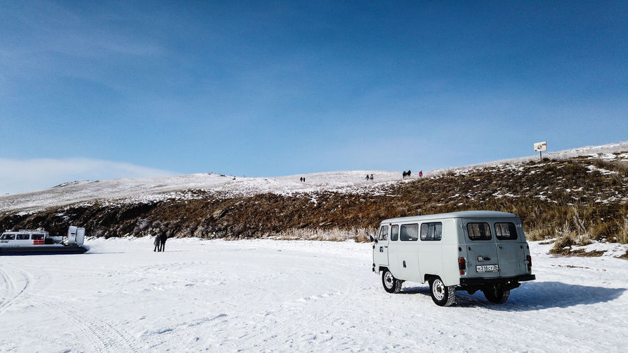 Car on snow covered mountain against blue sky