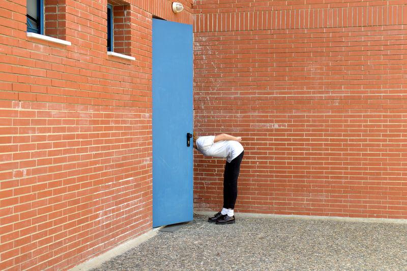 Side view of woman looking through open door