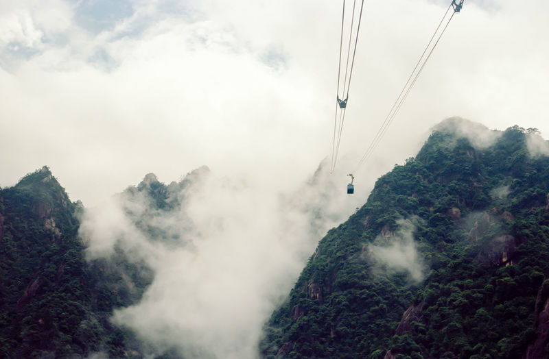Film Adventure Beauty In Nature Cable Cable Car China Cloud - Sky Day Environment Extreme Sports Fog Freedom Huangshan Leisure Activity Mountain Nature One Person Outdoors Overhead Cable Car Plant Real People Scenics - Nature Sky Tranquil Scene Tree