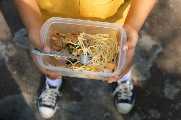 Spaghetti Food Take Out Food Box - Container Lunch Box Child Boy Sneakers Noodles One Person Food And Drink Holding High Angle View Real People Freshness Lifestyles Leisure Activity Human Hand Hand Container Human Body Part Vegetable Day Midsection Standing Healthy Eating Outdoors Tray